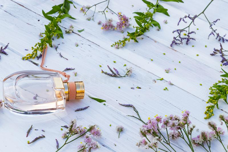 Perfume bottle surrounded by fresh flowers on wooden background stock image