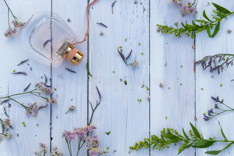 Perfume bottle surrounded by fresh flowers on wooden background royalty free stock photography