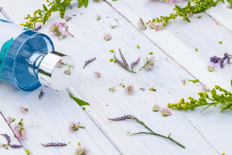 Perfume bottle surrounded by fresh flowers on wooden background royalty free stock image