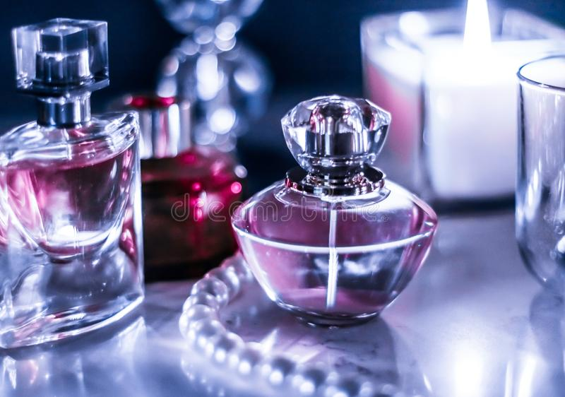 Perfume bottle and vintage fragrance on glamour vanity table at night, pearls jewellery and eau de parfum as holiday gift, luxury stock images