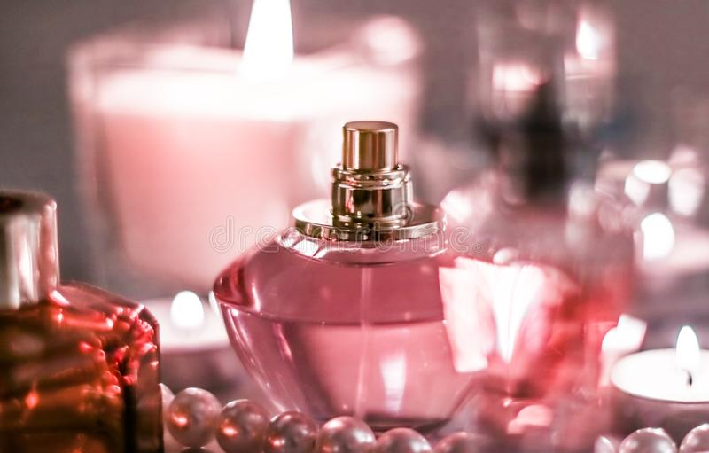 Perfume bottle and vintage fragrance on glamour vanity table at night, pearls jewellery and eau de parfum as holiday gift, luxury royalty free stock images