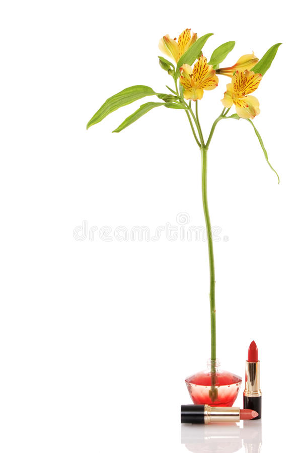 Perfume bottle, yellow flower and two red lipstick royalty free stock image