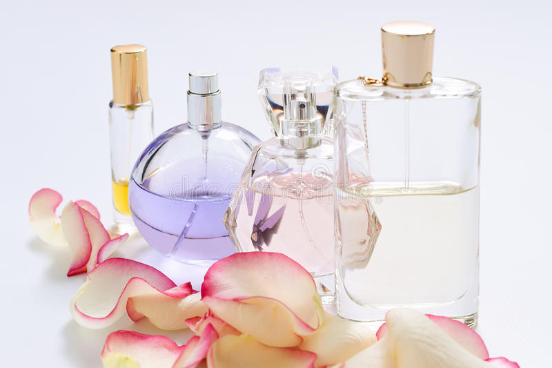 Perfume bottles with flower petals on light background. Perfumery, fragrance collection. Women accessories. royalty free stock image