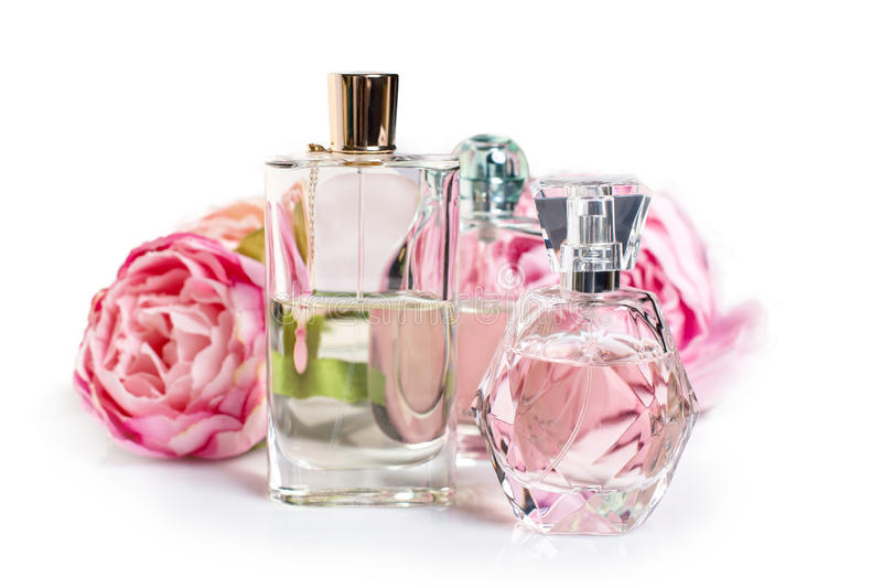 Perfume bottles with flowers on light background. Perfumery, cosmetics, fragrance collection.  royalty free stock image