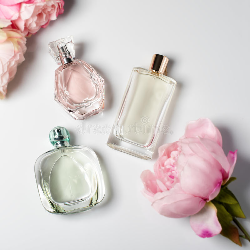 Perfume bottles with flowers on light background. Perfumery, cosmetics, fragrance collection. Flat lay.  stock images