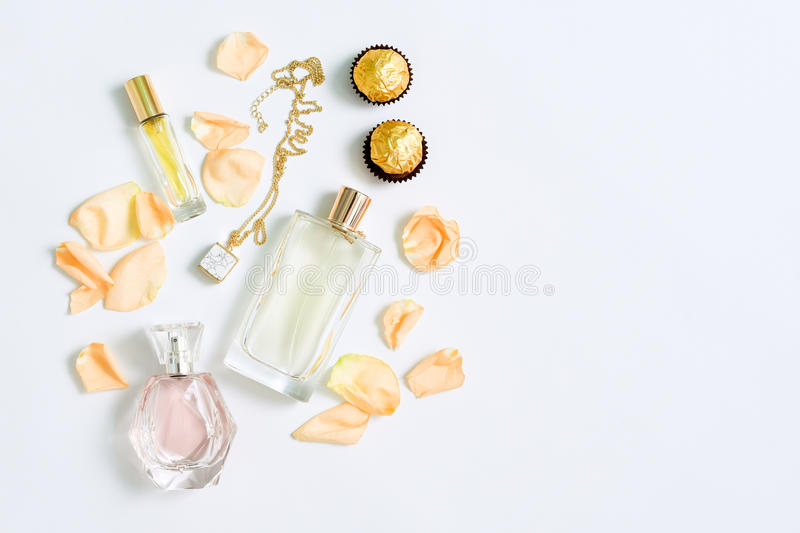 Perfume bottles with flowers petals on white background. Perfumery, cosmetics, jewelry and fragrance collection royalty free stock images