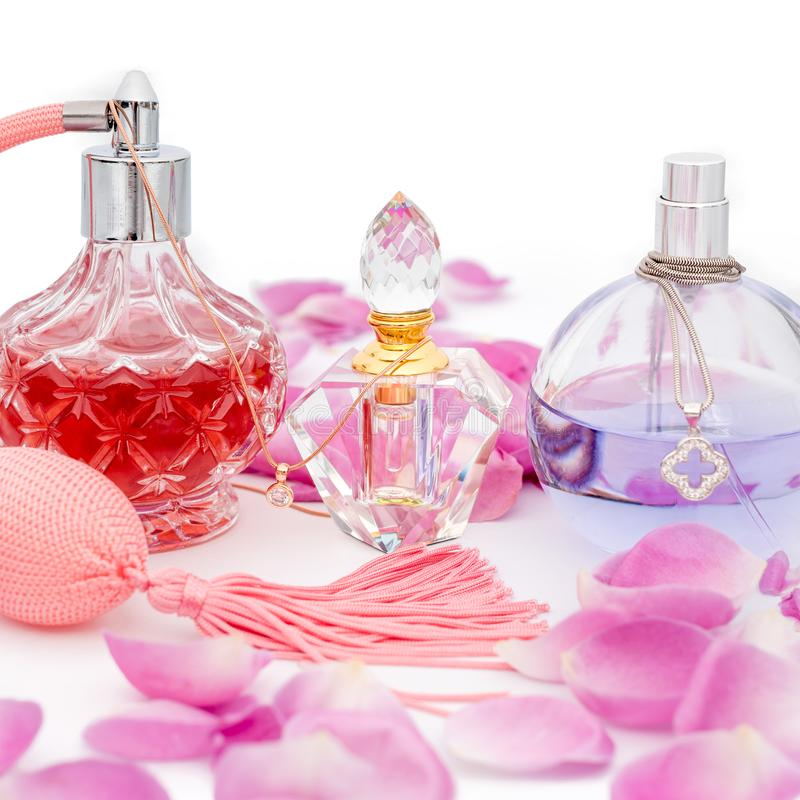 Perfume bottles with necklaces among flower petals on white background. Perfumery, cosmetics, fragrance collection royalty free stock images