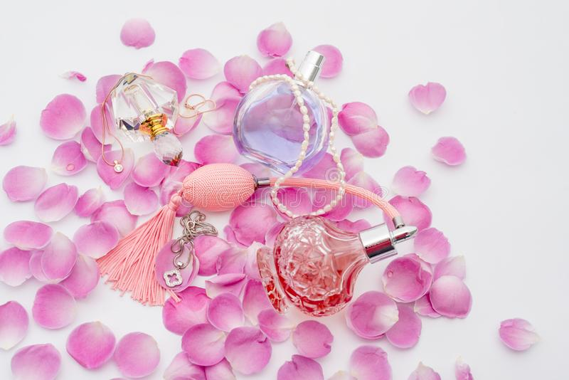 Perfume bottles with necklaces among flower petals on white background. Perfumery, cosmetics, fragrance collection royalty free stock photos