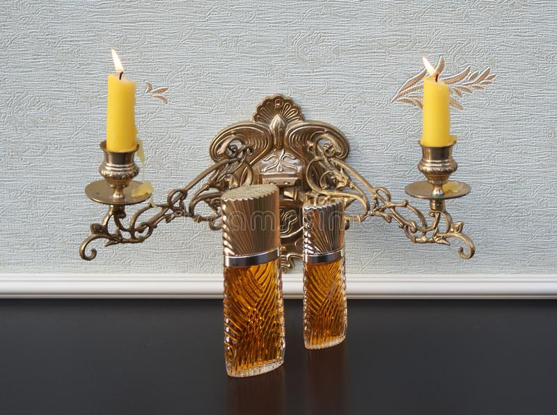 Diva, fragrance for ladies, large perfume bottle next to a commercial perfume bottle in front of a candelabra with shining candles. The perfume Diva is royalty free stock photo