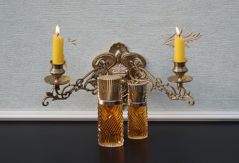 Diva, large perfume bottle next to a commercial perfume bottle in front of a piano candelabra with shining candles. The perfume Diva is distributed by Emanuel stock photos