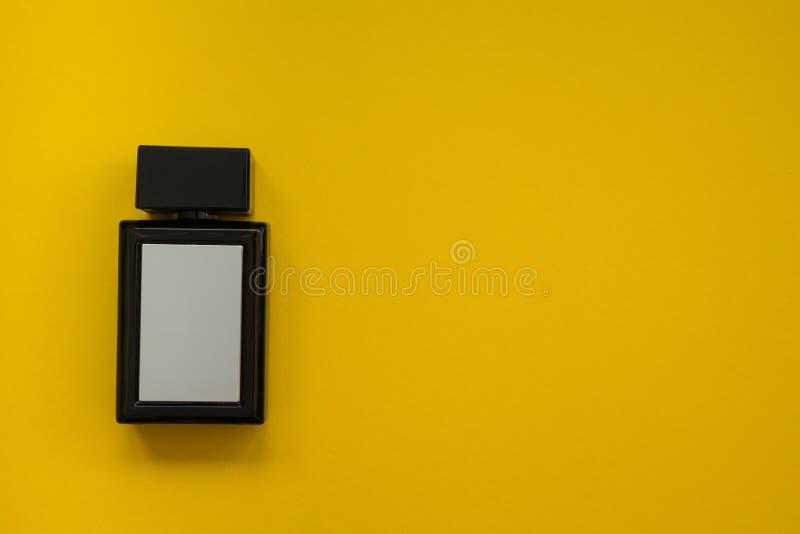 Perfume en la botella negra hermosa en un fondo amarillo, compozition plano fotos de archivo