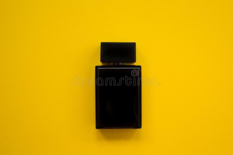 Perfume en la botella negra hermosa en un fondo amarillo, imagen plana imagenes de archivo