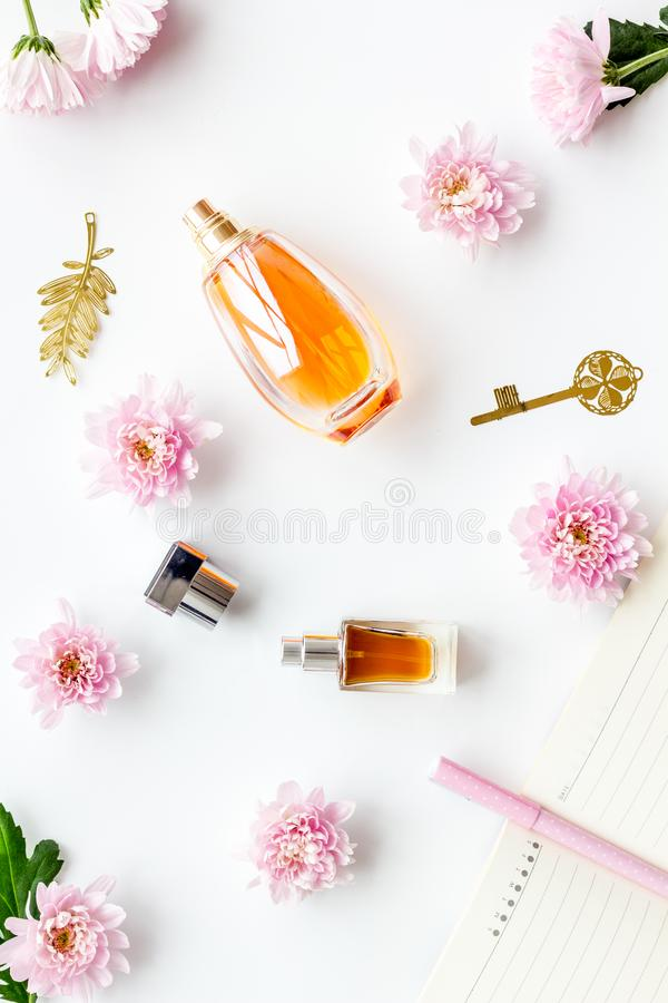 Perfume on feminine desk. Women`s accessories. Perfume near notebook for dairy, vintage key among flowers on white stock photos