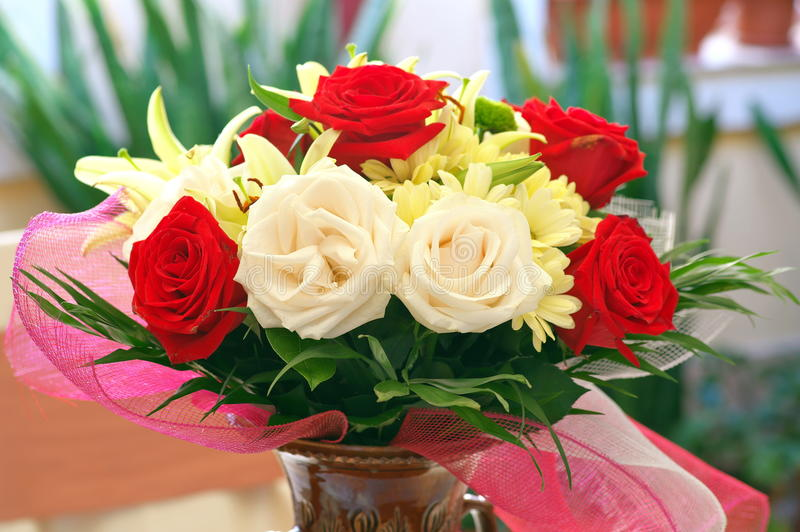 Perfume. Flower fragrance. Floral arrangement. Lovely perfumed bouquet with red roses, chrysanthemums and lilies in ceramic vase stock image