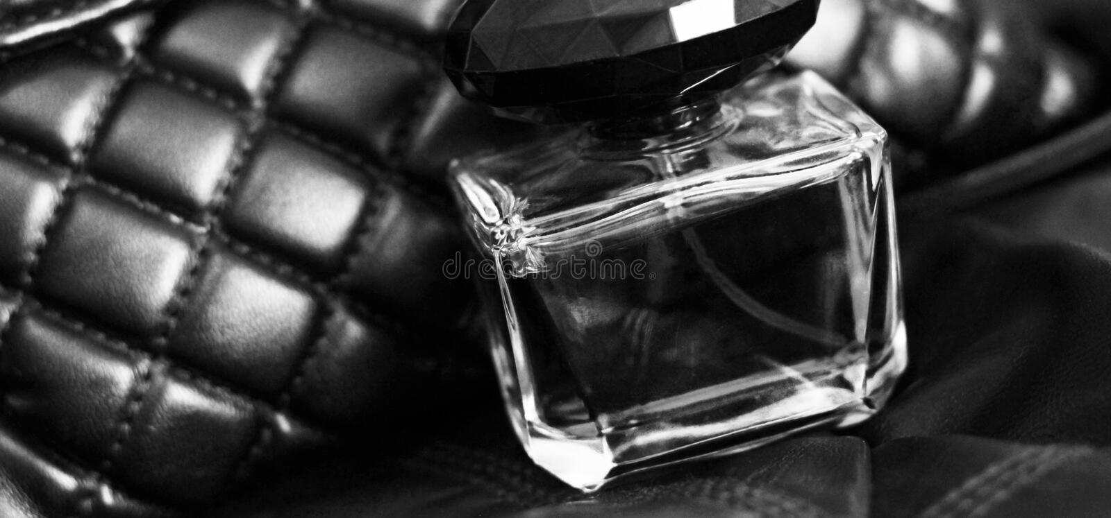 Perfume in glass on leather bag, black and white royalty free stock images