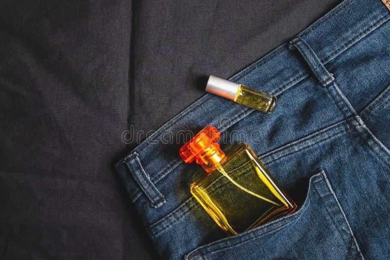 Perfume las botellas y las fragancias en bolsos de los vaqueros fotografía de archivo