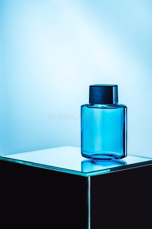 perfume para hombre en botella azul del espray, fotografía de archivo