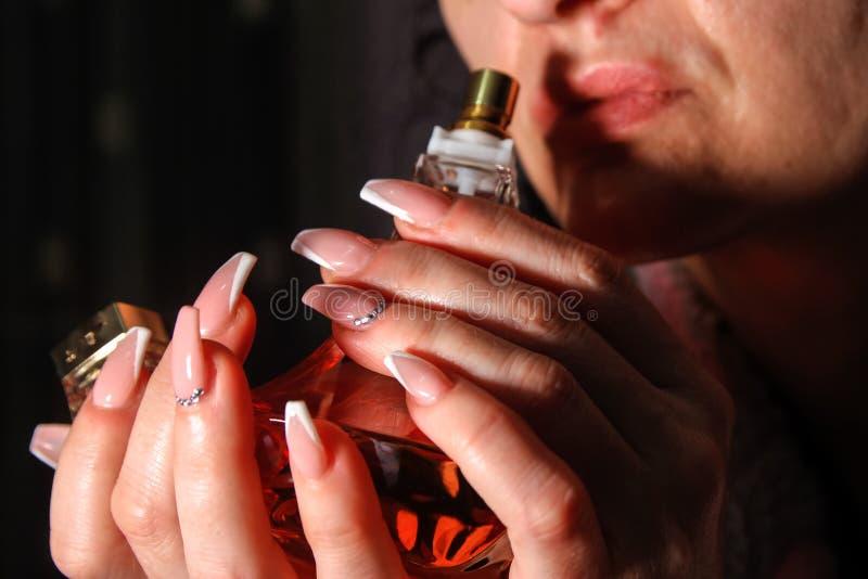 Perfume que huele de la mujer joven de una botella imagenes de archivo
