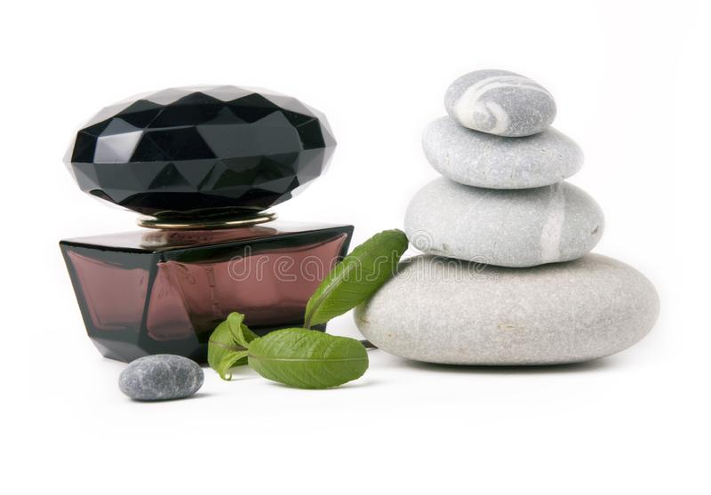 Perfume, stones and green leafs