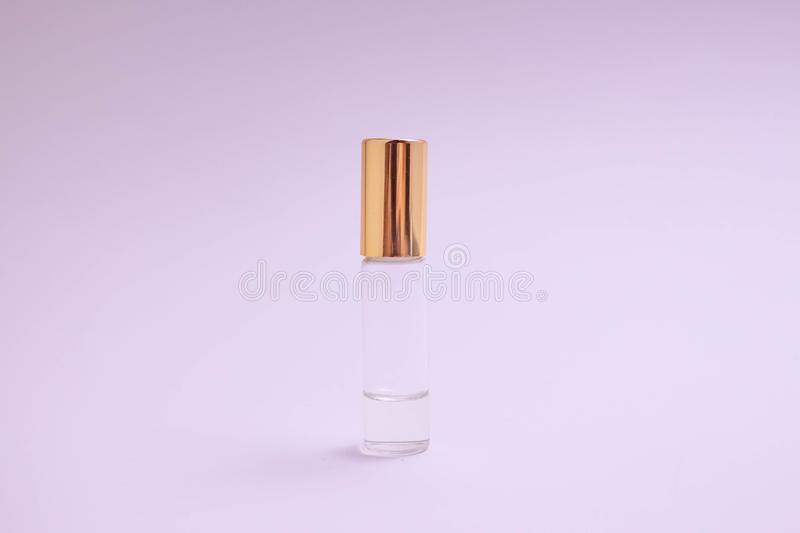 Perfume tester. Small perfume glass bottle with gold cap. Space text. The concept of minimalism. mockup. stock photos