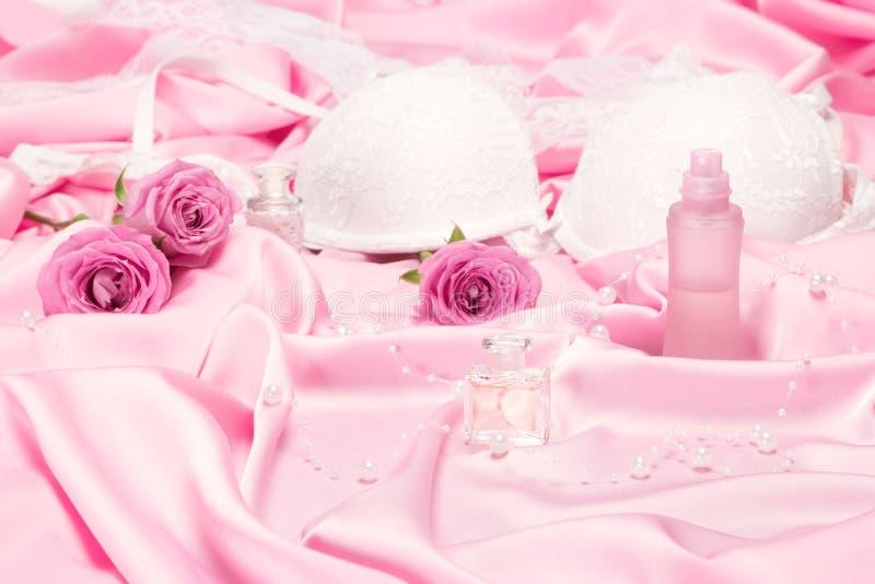 Perfumes com rosas e roupa interior das mulheres na seda cor-de-rosa fotos de stock