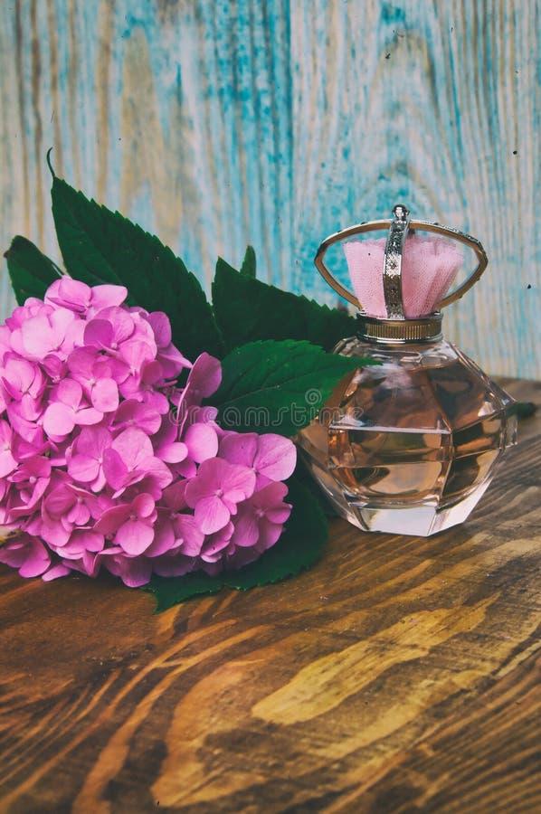 Perfumes e hortênsia em um fundo de madeira azul foto de stock