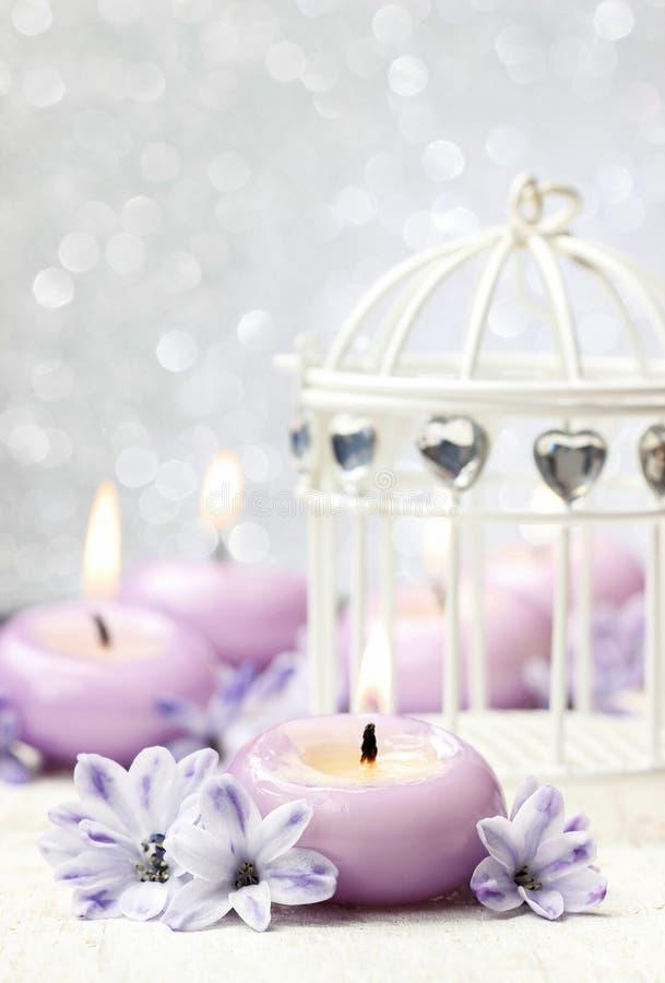 Perfumowy świeczki i rocznika birdcage wśród hiacyntowych kwiatów zdjęcie stock