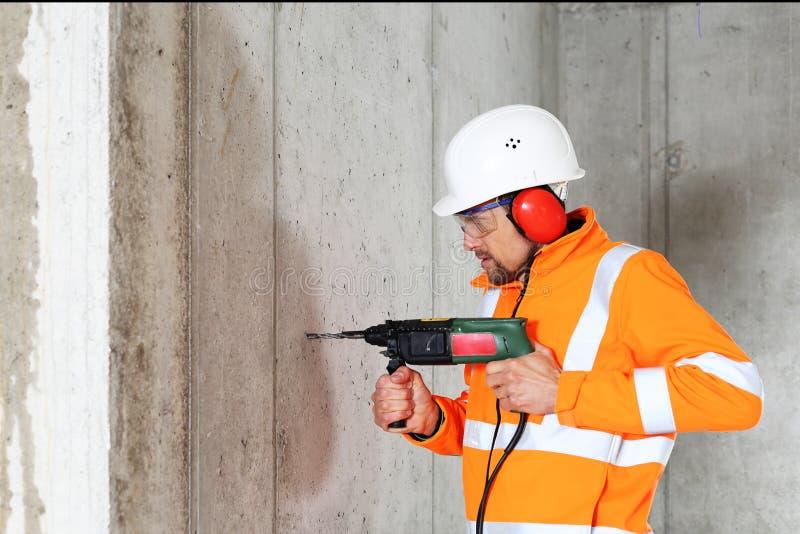 Perfuração do homem do trabalhador no concreto em um canteiro de obras imagens de stock