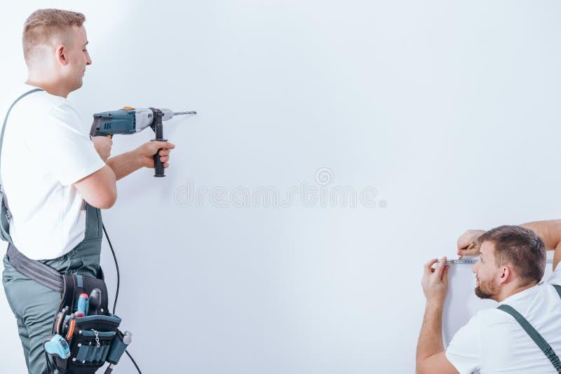 Perfuração do trabalhador do grupo da renovação foto de stock