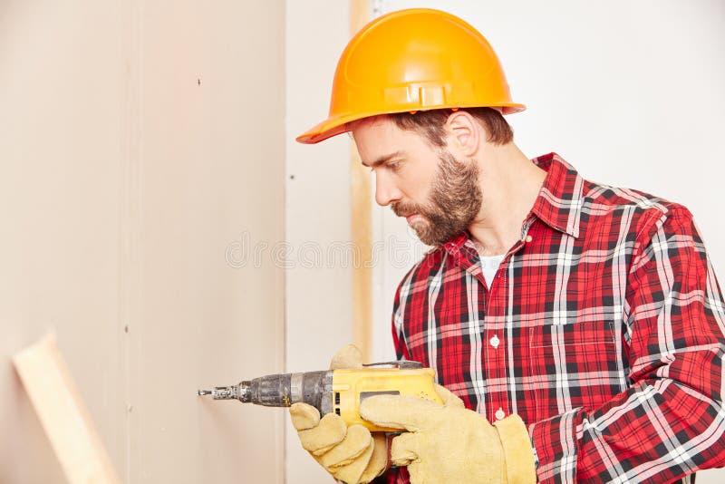Perfuração do trabalhador qualificado durante a renovação foto de stock royalty free