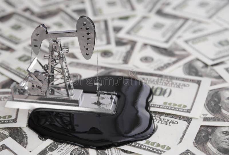 Perfuração para a exploração do petróleo uma bomba em um fundo do dólar com cédulas do dinheiro fotos de stock royalty free