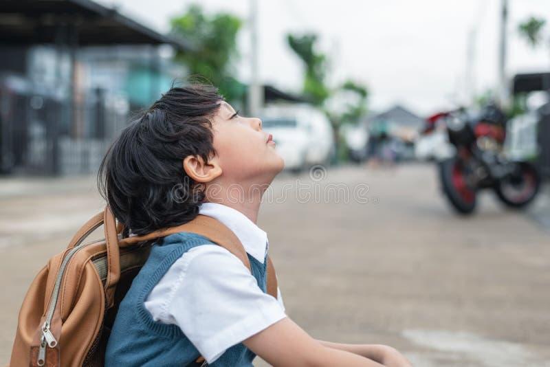 Perfura??o do rapaz pequeno a ir educar na manh? Os estudantes das crian?as que t?m o enfado comprimem dentro a emo??o Povos e co fotografia de stock
