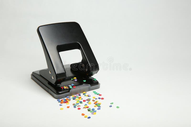 Perfurador de furo preto do escritório com confetes no fundo branco imagem de stock royalty free