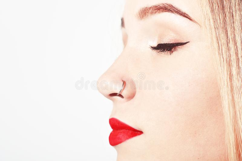 Perfurar no nariz Close up de uma cara do ` s da jovem mulher com a perfuração que pendura de seu nariz Retrato da menina do adol foto de stock royalty free