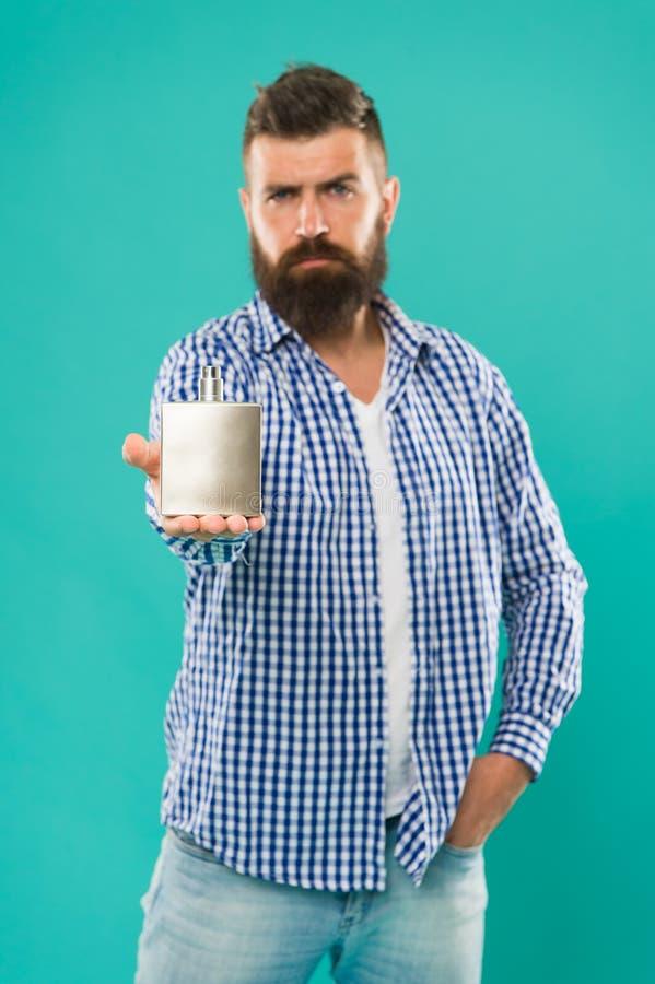 Perfusiereclame Gedekte man houdt parfum vast keulen ruikt lekker Cosmetisch voor mannen hipster man grooming mannetje royalty-vrije stock foto