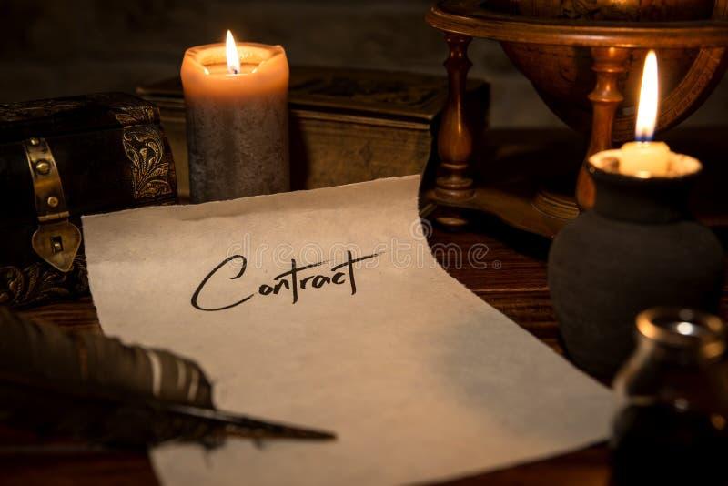 Pergamentpapper med en vingpenna och ett färgpulver, stearinljus och medeltida dekor fotografering för bildbyråer