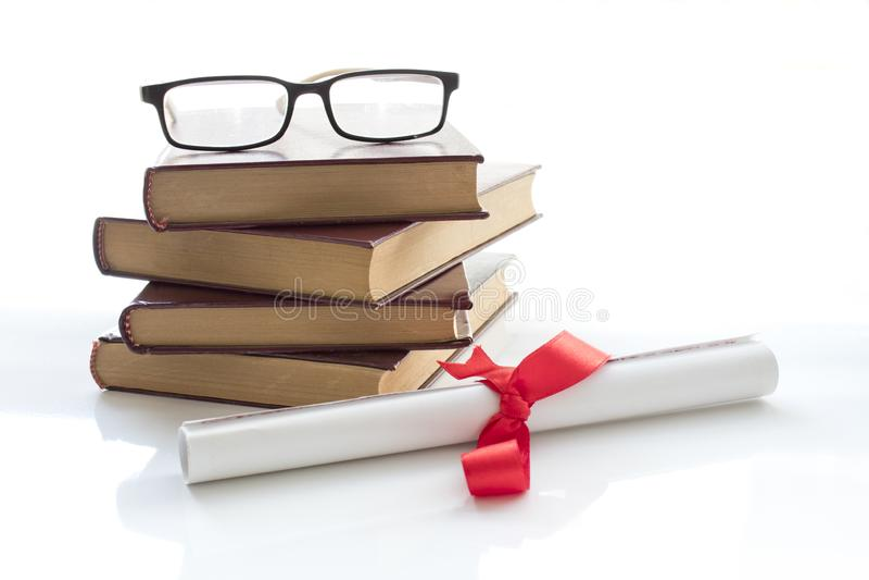 Pergaminowa dyplom ślimacznica, staczająca się w górę czerwonego faborku obok sterty książki na białym tle z fotografia royalty free