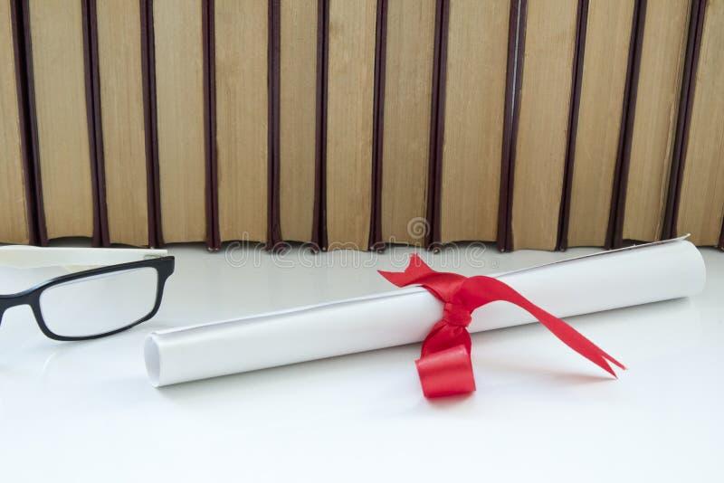Pergaminowa dyplom ślimacznica, staczająca się w górę czerwonego faborku obok sterty książki na białym tle z obraz royalty free