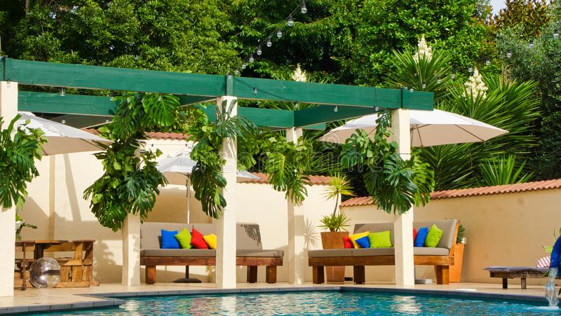 Pergola`s around a pool. A luxury home with pool, outdoor furniture and lush tropical trees. Colourful cushions royalty free stock images