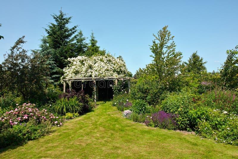 Pergolagazebo i en härlig trädgård royaltyfri bild
