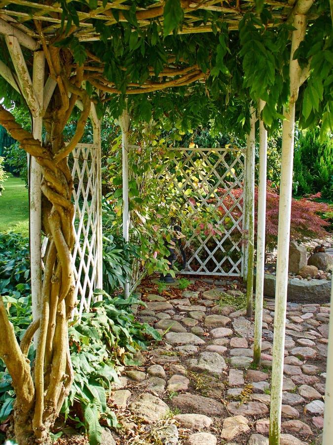 Pergolagazebo i en härlig trädgård royaltyfri foto