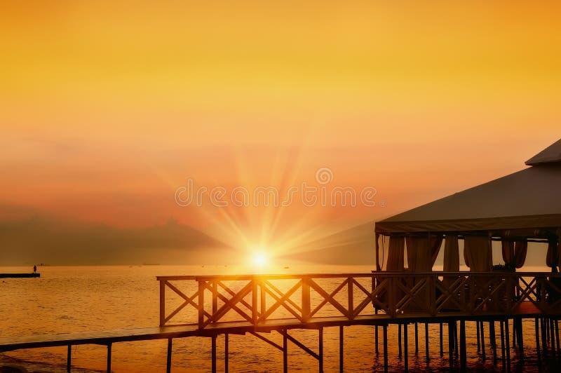Pergolaveranda op stelten op het strand bij dageraad stock foto's