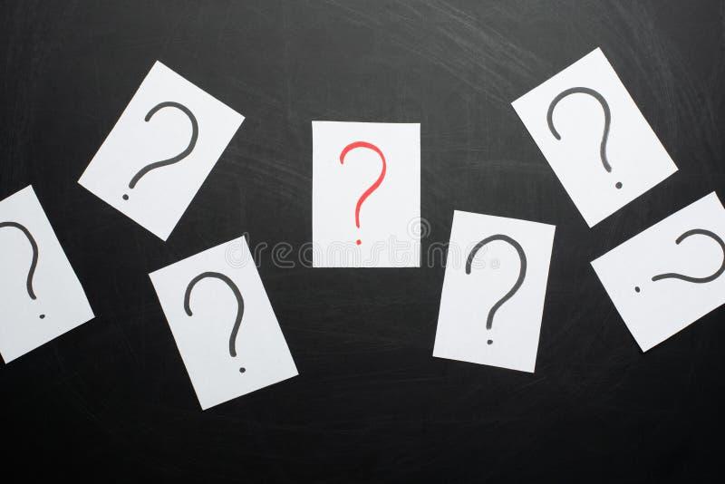 Perguntas demais Pilha de notas de papel coloridas com pontos de interrogação closeup imagens de stock