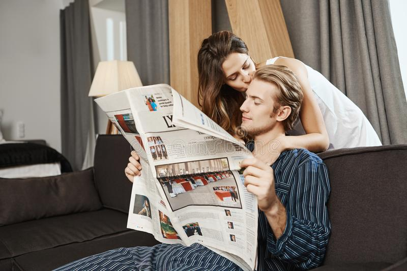 Periódico apuesto de la lectura de los pares en sala de estar antes del individuo hermoso del desayuno que comprueba noticias cua fotos de archivo libres de regalías