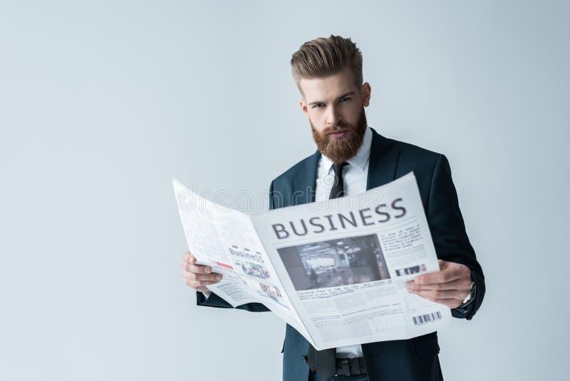 Periódico barbudo de la lectura del hombre de negocios en gris fotos de archivo libres de regalías