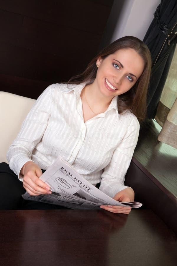 Periódico de la lectura de la mujer foto de archivo