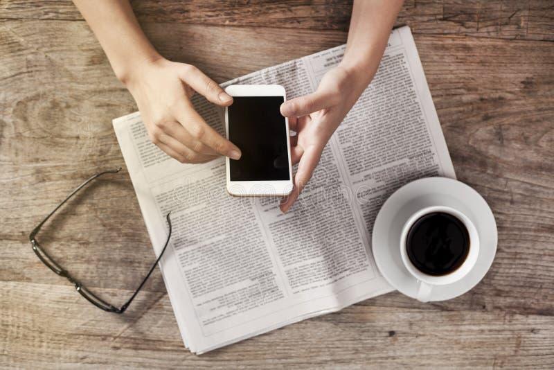 Periódico de la lectura de la mujer joven y teléfono de la tenencia imagen de archivo libre de regalías