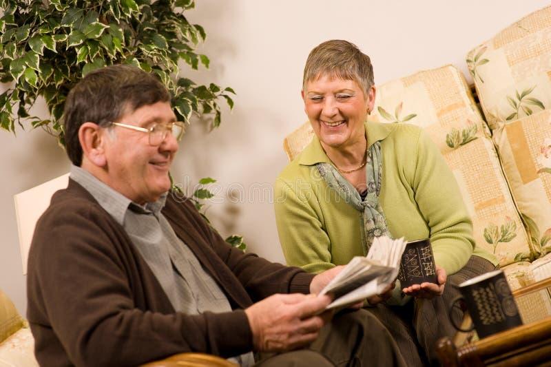 Periódico de la lectura de los pares del hombre mayor y de la mujer imagen de archivo libre de regalías