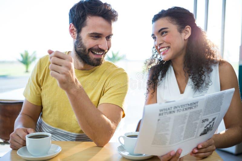 Periódico de la lectura de los pares mientras que comiendo café imagen de archivo