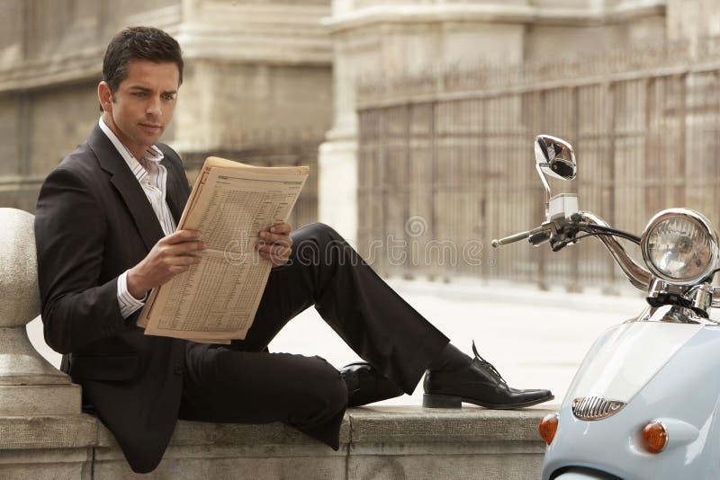 Periódico de la lectura de Sitting By Scooter del hombre de negocios fotografía de archivo libre de regalías